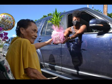 """A gift-giver hands a present to Curline Lyon during a drive-through birthday celebration outside her Kingston home on Saturday. Lyon, whose family raves about her """"legendary dumplings"""", turns 100 today, coming full circle to survive two of the most deadly"""