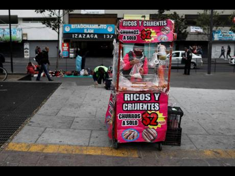 A vendor, wearing a protective face mask, is bundled up against the cold as she prepares churros in her mobile stall in Mexico City, Wednesday, November 18, 2020, amid the new cornavirus pandemic.