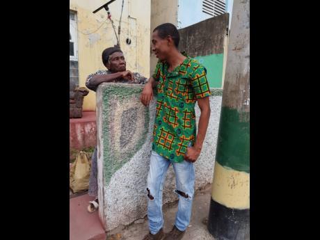 Jermaine Cowie greeting an elderly West Kingston resident