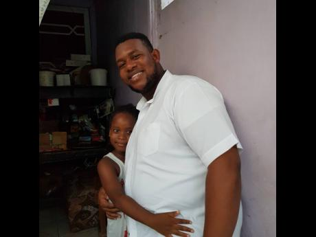 Shemar Miller shares a moment with a young girl after giving care packages to her family in West Kingston