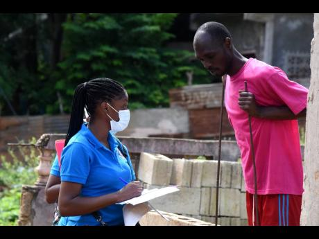 A healthcare worker interacts with a resident of Frazer's Content, St Catherine, on Saturday as community surveillance was conducted in the community to raise awareness and test persons for the virus.
