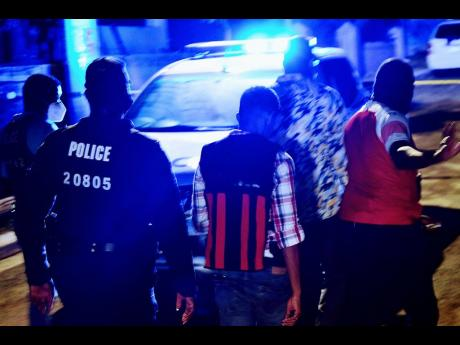Police personnel investigate a triple murder in Tryall Heights, near Lauriston, St Catherine, on Sunday evening. Two girls and their grandmother were slain.