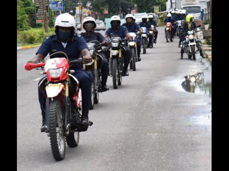 Members of the Jamaica Constabulary Force motorcycle unit engage in a training ride along Brunswick Avenue in Spanish Town on Tuesday. A man was slain on the road on Monday, one of eight people killed in the St Catherine North Police Division over 48 hours