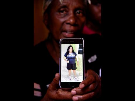 Angella Christine Holmes shows a picture of her daughter, Janice Ellison-Reid, who was shot and killed by gunmen at her home in Thompson Pen, Spanish Town, on Monday afternoon.
