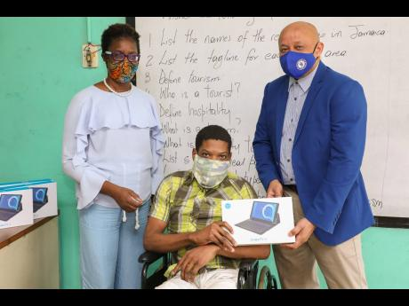 Mark Chisholm (right), Sagicor Foundation director, presents a  tablet to Damarie Thomas (centre), student of the Abilities Foundation, on November 13 at the special education institution. Thomas and four other students received tablets from the Sagicor Fo