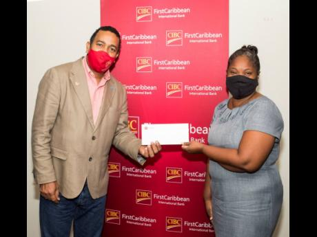 Teacher Youlanda Duffus (right), representing the Trench Town Primary School, accepts a cheque from Nigel Holness, managing director of the CIBC FirstCaribbean International Bank, in support of the construction of a tuck shop at the school.  Approximately