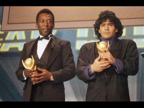 """FILE - In this March 1987 file photo, Pele, left, and Maradona hold """"Sports Oscar"""" trophies in Milan, Rome. The Argentine soccer great who was among the best players ever and who led his country to the 1986 World Cup title before later struggling with"""