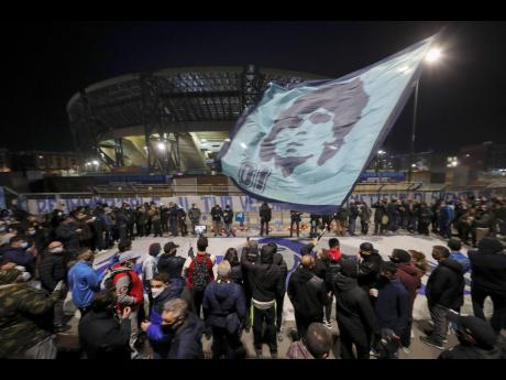 People gather outside the San  Paolo Stadium to  pay homage to late football legend Diego Maradona, in Naples, Italy, yesterday. Maradona was 60.