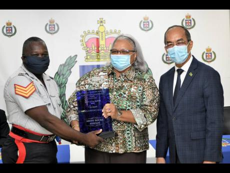 Sergeant Garfield Wallace of the Above Rocks Police Station in St Catherine North accepts the Top Station Award from Jacqueline Hinkson, chairman of the Police (Civilian Oversight) Authority (PCOA), as National Security Minister Dr Horace Chang looks on. T