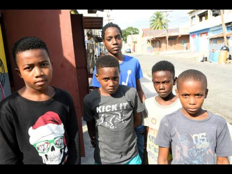 From left: Devrughn Davis, Dayvion Campbell, Dimanie McFarlane, Deeon Williams and Odane Hill, (standing at back) talk to The Gleaner on Thursday about what they want for Christmas. The youngsters live in the troubled Tel Aviv community in downtown Kingsto