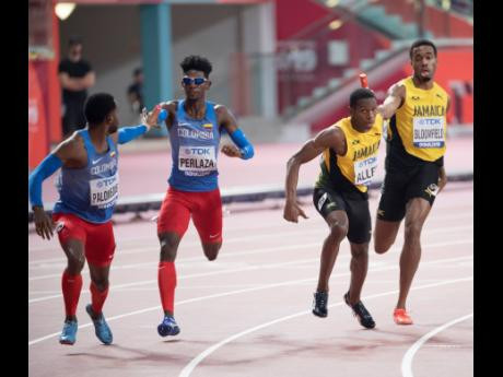 Jamaica's Nathon Allen collects the baton from teammate Akeem Bloomfield in the first exchange of the men's 4x400m relay final at the World Athletics Championships in Doha, Qatar on Sunday, October 6, 2019. Jamaica Athletics Administrative Association