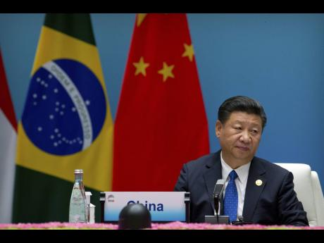 Chinese President Xi Jinping listens to a speech during the BRICS Dialogue of Emerging Market and Developing Countries