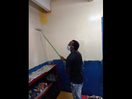 Andrew Folkes painting a classroom at the Nannyville Basic School in St Andrew