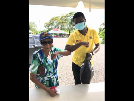 Leon Malcolm greets an elderly resident and gives her a care package.