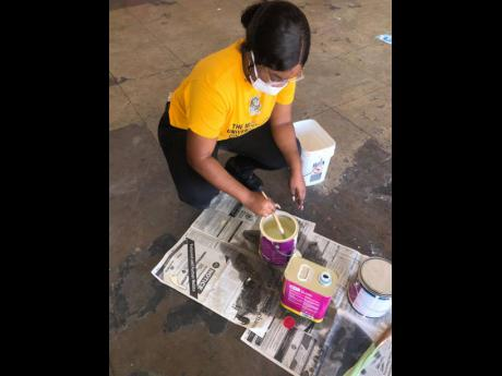 Yanique Tracy mixing paint to take on her project.
