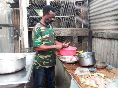 Michael Deen, Jasmine Deen's uncle, preparing food for her 23rd birthday celebration yesterday at the family's 10 Miles, Bull Bay, St Andrew home.