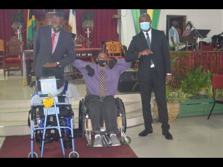 Andrew East (in wheelchair), president of the Cornwall Combined Disabilities Association (CCDA), in a photo op with the Reverend Courtney Walters (left), pastor of Calvary Baptist Church in Montego Bay, St James, and Labour and Social Security State Minist