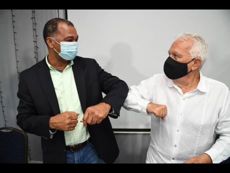 Presidential Elbows: Charles Johnston (right), immediate past president of the Shipping Association of Jamaica (SAJ), welcomes William Brown to the post of president of the SAJ at the association's 82nd annual general meeting on Friday, November 27 at th