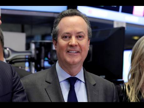 In this April 28, 2016 file photo, S&P Global CEO Douglas Peterson poses for photos on the floor of the New York Stock Exchange.