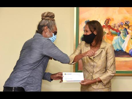 RJRGLEANER Sports Foundation member Molly Rhone presents a Benevolent Fund cheque to Jamaica Surfing Association President Anthony Wilmot at the RJRGLEANER Communications Group headquarters in St Andrew yesterday. The presentation was made to assist Wilmot