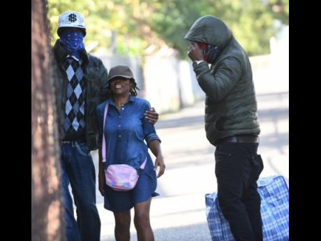 A deportee, with face covered, is met by a relative at Harman Barracks in Kingston in February. Dozens of Jamaicans are expected to arrive from Britain today.