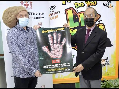 Minister of National Security Horace Chang (right) and artiste Alborosie hold the poster promoting the single 'Shadows after Dark'.