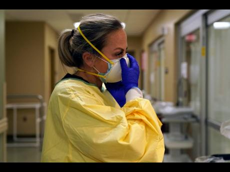 In this November 24 photo, Registered Nurse Chrissie Burkhiser puts on personal protective equipment as she prepares to treat a COVID-19 patient in the emergency room at Scotland County Hospital in Memphis, Missouri.