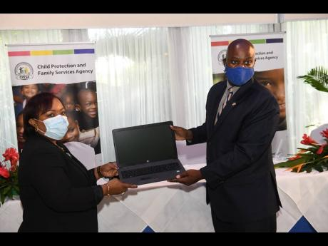 USAID Country Representative Jason Fraser makes a presentation of one of 80 laptops to CEO of the Child Protection and Family Services Agency, Rosalee Gage-Grey, during the opening ceremony of the agency's 2020 Annual Digital Field Services Conference on W