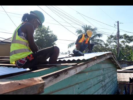 Jermaine McKay (right) and Garfield Campbell volunteered their time and skill to install a new roof on the house of Dwayne Walker and his wife, Staniece, in Ellerslie Pen, Spanish Town, on Wednesday. The couple's heart-tugging story of love and their ord