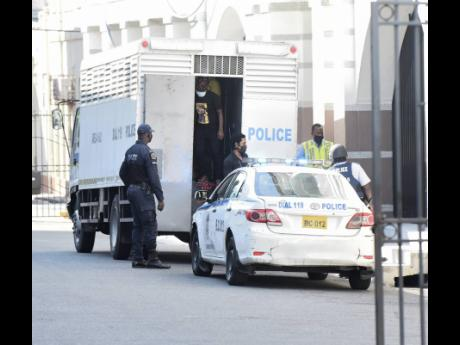 Detainees are escorted towards the Supreme Court building in Kingston on Wednesday. Uchence Wilson and eight of his cronies were sentenced for various crimes by Chief Justice Bryan Sykes.