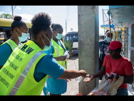 Public health aides sanitise the hands of a snacks vendor as they prepare to give her a mask outside the Coronation Market in downtown Kingston yesterday during a COVID-19 sensitisation and testing initiative.