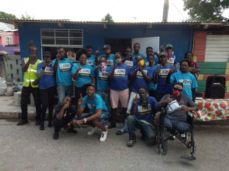 Akino Page (stooping, second left) and most of the core members of the Dream Team pose for a photo last Friday outside their latests completed project, a 'chef shop' in Trench Town, St Andrew.