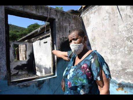 Miriam Lindsay gestures towards a room in her razed house in Hermitage on Sunday.