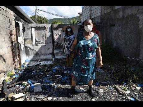 Miriam Lindsay, a triple amputee, stands what remains of her bedroom in the burnt-out shell of her home in Hermitage, near August Town, in St.Andrew. Lindsay lost everything in the fire and is now seeking help to rebuild.