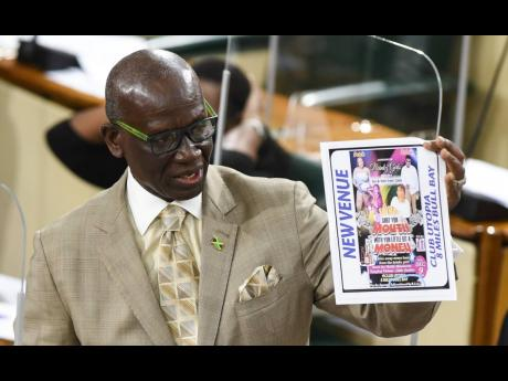 Minister of Local Government and Rural Development Desmond McKenzie holding a flyer advertising a party in contravention of Jamaica's coronavirus laws.