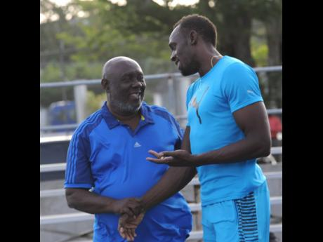 In this file photo from June 2016, Usain Bolt (right) has a light moment with coach Glen Mills during a Racers Track Club training session at the UWI/Usain Bolt Track on the UWI Mona Campus.