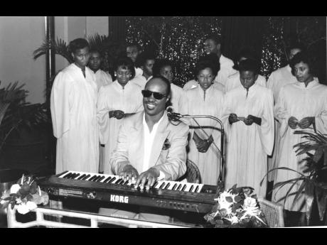 Playing the keyboard, Stevie Wonder performs with a Jamaican choir during the 1990 Motown Soul by The Sea. His performance, although listed as an event surprise was deliberately not advertised.