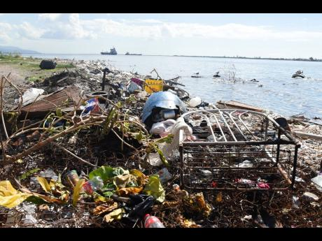 A section of the Rae Town fishing beach is seen covered with garbage yesterday. Pollution has caused a decline in the amount of fish they have been able to catch in the area.