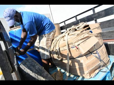 Orville Morris loads his van with a barrel and boxes at the Kingston Wharves in Kingston on Tuesday.