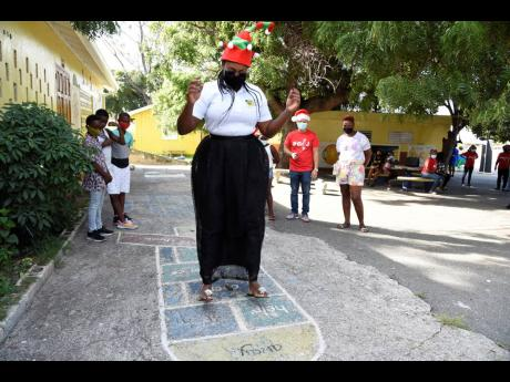 Juliet Holness, member of parliament for East Rural St Andrew, shows her skills in a game of hopscotch on the day that she took part in the presentation of care packages to Harbour View- and Bull Bay-based students.