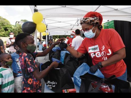 Arlene Miller (right), a member of the Progressive Grocers of Jamaica Limited, helps Darren Crosbale to look through a care package that would better suit him. The handover of care packages to students residing in Harbour View and Bull Bay took place at th