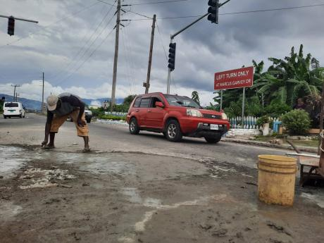Shoemaker Almando Bailey (yellow shorts) and friends using cement to patch a section of Chesterfield Drive in Seaview Gardens, St Andrew, last Friday. Motorists had been frequently swerving to potholes along the stretch, increasing the likelihood of colli