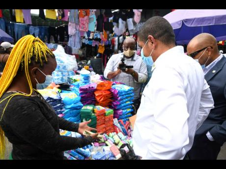 Mayor of Kingston Delroy Williams (second right) and Robert Hill (right), CEO of the Kingston and St Andrew Municipal Corporation, don masks as they engage with a vendor while touring sections of downtown Kingston to observe the level of compliance to COV