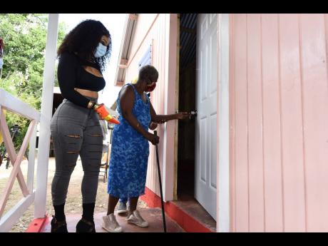Dancehall superstar Shenseea (left), brand ambassador for Boom, escorts Joan Willie into her new home built by Food For The Poor in conjunction with Wisynco as part of the energy drink's 10th anniversary celebrations.