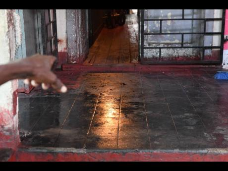 A man points to the location where a severed human hand was discovered at a Kingston Garden premises on Friday morning.