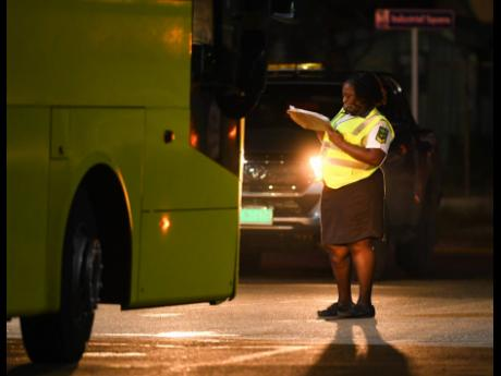 A security guard checks Jamaica Urban Transit Company buses entering a restricted area of the Norman Manley International Airport on Monday evening. The buses were deployed to transport passengers who came on a British Airways flight and will be taken into