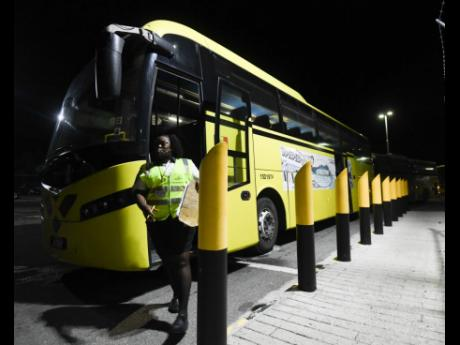 A security guard walks past one of several Jamaica Urban Transit Company buses deployed to transport travellers from the United Kingdom to quarantine in St Ann.