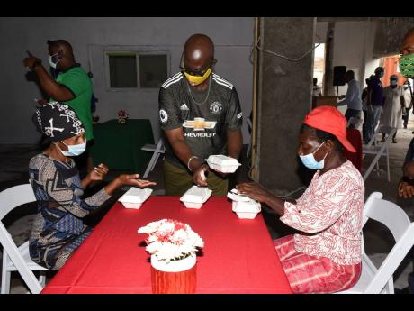 Desmond McKenzie (centre), minister of Local Government and Rural Development, serves meals to Arlette Allen (left) and Sylvia Nelson (right), members of the indigent community who attended the official launch of the Kingston and St Andrew Municipal Corpor