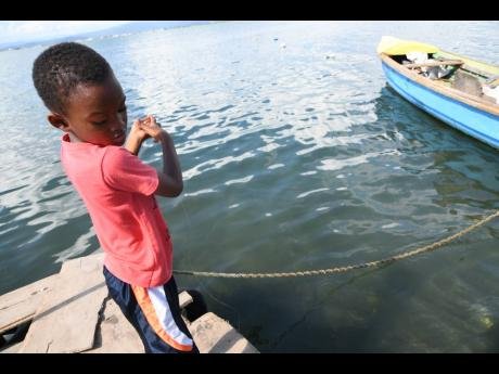 Adonai Smith line-fishing in Port Royal on Tuesday. Fisherfolk blame dwindling catch on dredging and the anchoring of ships in sensitive areas.
