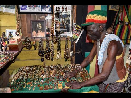 Glenford Bennett shows off some of his craft items inside his 23 Third Street shop in Trench Town, Kingston.